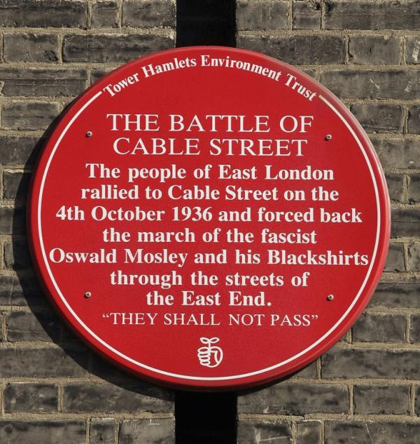 A plaque commemorating the Battle of Cable Street is mounted on a wall in London, England