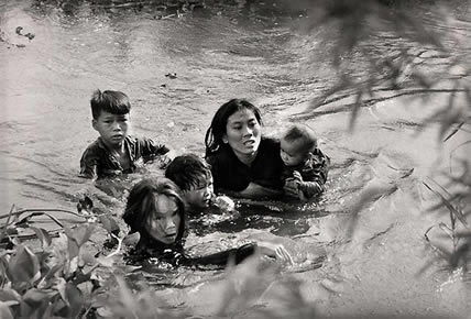 1965. A mom and her ‎children try to cross the river in South Vietnam in an attempt to run away from the American ‎bombs, photo by Kyoichi Sawada