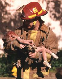 Fireman Chris Fields holding the dying infant Baylee Almon - symbol of the tragedy.