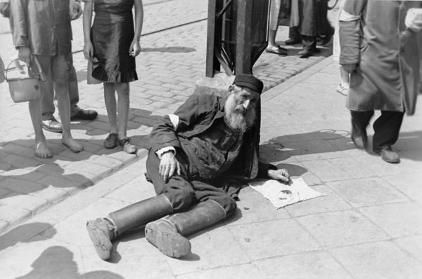 An elderly Jewish man on the sidewalk of the Warsaw Ghetto